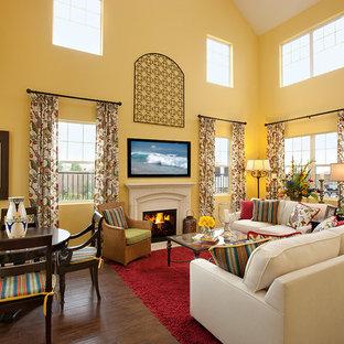 Ispirazione per un ampio soggiorno mediterraneo con pareti gialle, parquet scuro, camino classico, cornice del camino in pietra e TV a parete