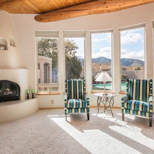 Idée de décoration pour un salon sud-ouest américain de taille moyenne et ouvert avec une salle de réception, un mur beige, moquette, une cheminée d'angle, un manteau de cheminée en plâtre et un téléviseur encastré.