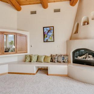 アルバカーキの中サイズのサンタフェスタイルのおしゃれなLDK (フォーマル、ベージュの壁、カーペット敷き、コーナー設置型暖炉、漆喰の暖炉まわり、埋込式メディアウォール) の写真