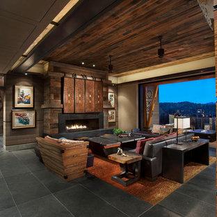 Imagen de salón para visitas abierto, de estilo americano, grande, con paredes marrones, chimenea lineal, marco de chimenea de piedra, televisor retractable, suelo negro y suelo de pizarra