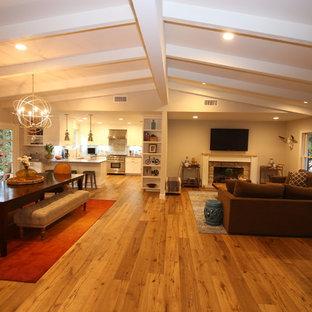 Esempio di un ampio soggiorno minimalista aperto con pareti bianche, pavimento in legno massello medio, camino classico, cornice del camino in mattoni, TV a parete e sala formale