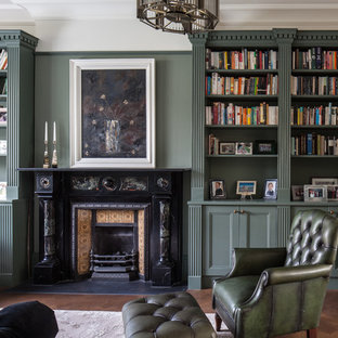 Medium sized traditional enclosed living room in London with green walls, dark hardwood flooring, a standard fireplace, a metal fireplace surround and brown floors.