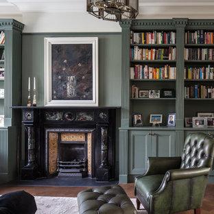 Ispirazione per un soggiorno tradizionale di medie dimensioni e chiuso con pareti verdi, parquet scuro, camino classico, cornice del camino in metallo e pavimento marrone