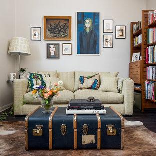 Ispirazione per un piccolo soggiorno eclettico aperto con libreria, pareti bianche, parquet scuro, nessun camino, nessuna TV e pavimento nero