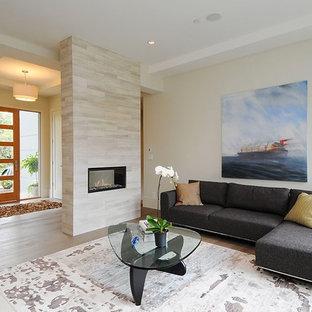 Immagine di un soggiorno minimalista con pareti beige e camino bifacciale