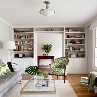 Imagen de biblioteca en casa cerrada, tradicional renovada, de tamaño medio, sin chimenea y televisor, con paredes grises y suelo de madera en tonos medios