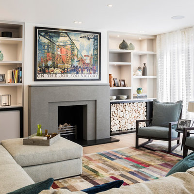 Example of a mid-sized transitional enclosed medium tone wood floor and brown floor living room design in London with beige walls, a standard fireplace, no tv and a stone fireplace