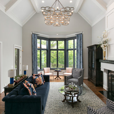 Example of a large classic formal medium tone wood floor and brown floor living room design in Kansas City with gray walls, a standard fireplace, a stone fireplace and no tv