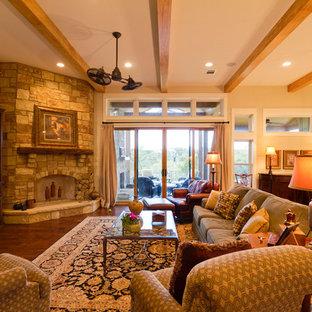 Idee per un grande soggiorno stile americano aperto con pareti beige, pavimento in legno massello medio, camino ad angolo, cornice del camino in pietra, parete attrezzata e pavimento marrone