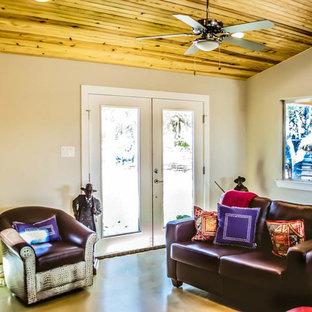 オースティンの小さいコンテンポラリースタイルのおしゃれなリビングロフト (ベージュの壁、コンクリートの床、標準型暖炉、石材の暖炉まわり、壁掛け型テレビ) の写真