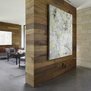 Cette image montre un salon design avec béton au sol et un mur en pierre.