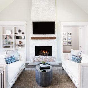 Idée de décoration pour un grand salon tradition ouvert avec un mur gris, un sol en bois foncé, une cheminée standard, un manteau de cheminée en pierre, un téléviseur fixé au mur et un sol beige.