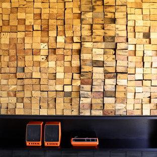 メルボルンの中くらいのコンテンポラリースタイルのおしゃれなLDK (フォーマル、黒い壁、コンクリートの床、薪ストーブ、金属の暖炉まわり、内蔵型テレビ) の写真