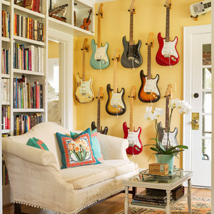 Photo of an eclectic living room in Little Rock with yellow walls, medium hardwood floors and brown floor.
