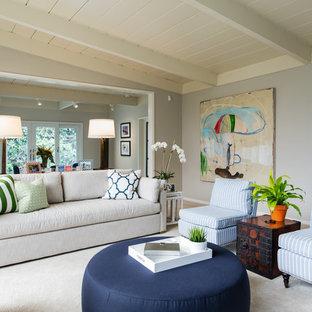Idee per un grande soggiorno chic aperto con pareti grigie, parquet chiaro, camino classico, cornice del camino in pietra, TV a parete e pavimento beige