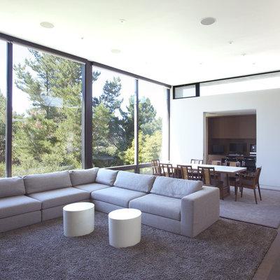 Minimalist open concept dark wood floor living room photo in San Francisco with white walls