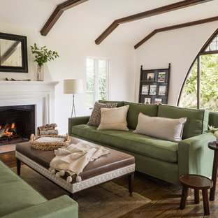 Design ideas for a mediterranean open plan living room in San Francisco with white walls, dark hardwood flooring, a standard fireplace, a plastered fireplace surround, no tv and brown floors.