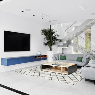 Large trendy open concept ceramic tile and gray floor living room photo in San Francisco with white walls and a wall-mounted tv