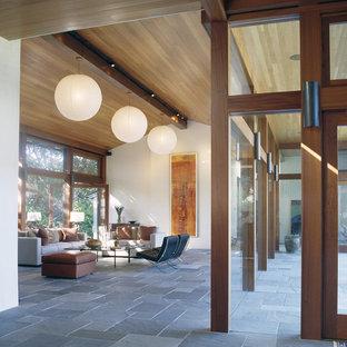 Ejemplo de salón abierto, moderno, sin televisor, con suelo de pizarra y suelo azul