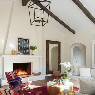 Idéer för att renovera ett medelhavsstil vardagsrum, med mörkt trägolv, en spiselkrans i gips, beige väggar, en standard öppen spis och brunt golv