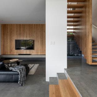 ブリスベンのモダンスタイルのおしゃれなLDK (白い壁、コンクリートの床、壁掛け型テレビ、グレーの床、板張り壁) の写真
