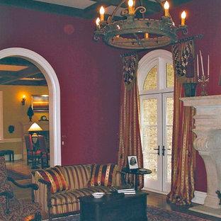 ローリーの大きい地中海スタイルのおしゃれなリビング (フォーマル、赤い壁、無垢フローリング、石材の暖炉まわり) の写真