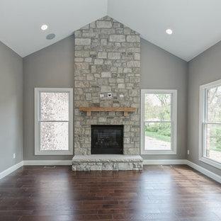 Aménagement d'un grand salon craftsman ouvert avec un mur gris, un sol en bois brun, une cheminée standard, un manteau de cheminée en pierre et un sol marron.