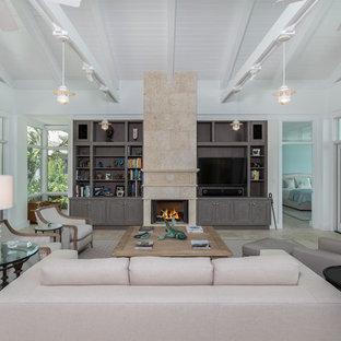 タンパの大きいビーチスタイルのおしゃれなLDK (白い壁、トラバーチンの床、標準型暖炉、石材の暖炉まわり、埋込式メディアウォール) の写真