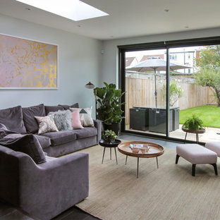 This is an example of a large contemporary open plan living room in London with dark hardwood flooring, no fireplace, a home bar, grey walls and black floors.