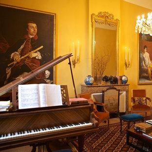 Foto di un grande soggiorno tradizionale aperto con pareti gialle, pavimento in legno massello medio, camino classico, nessuna TV, cornice del camino in pietra e sala della musica