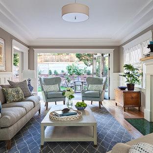 サンフランシスコのトラディショナルスタイルのおしゃれなリビング (茶色い壁、無垢フローリング、標準型暖炉、タイルの暖炉まわり、茶色い床) の写真