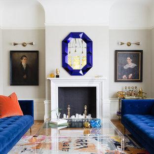 Diseño de salón para visitas cerrado, tradicional renovado, sin televisor, con suelo de madera en tonos medios, marco de chimenea de piedra, paredes grises, chimenea tradicional y suelo marrón