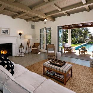 Modelo de salón abierto, mediterráneo, pequeño, con paredes blancas, suelo de cemento, chimenea tradicional y marco de chimenea de yeso