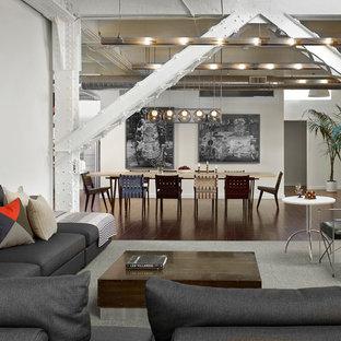 Ejemplo de salón abierto, industrial, extra grande, con suelo de madera en tonos medios y paredes blancas
