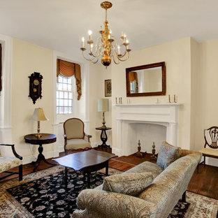 Immagine di un soggiorno classico di medie dimensioni e chiuso con sala formale, pareti beige, parquet scuro, camino classico, cornice del camino in legno, nessuna TV e pavimento marrone