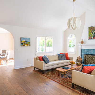 Example of a large transitional formal and enclosed medium tone wood floor and brown floor living room design in Los Angeles with beige walls, a standard fireplace, a tile fireplace and no tv