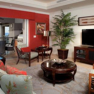 ハワイのトロピカルスタイルのおしゃれなLDK (赤い壁、ライムストーンの床、据え置き型テレビ) の写真