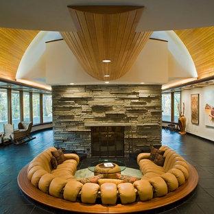 Aménagement d'un grand salon contemporain ouvert avec un mur blanc, un sol en ardoise, une cheminée standard, un manteau de cheminée en pierre, aucun téléviseur et une salle de réception.