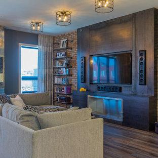 ニューヨークの大きいインダストリアルスタイルのおしゃれなLDK (グレーの壁、濃色無垢フローリング、横長型暖炉、金属の暖炉まわり、埋込式メディアウォール、茶色い床) の写真