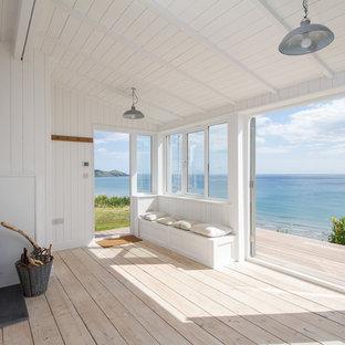 デヴォンの小さいビーチスタイルのおしゃれなLDK (白い壁、淡色無垢フローリング、薪ストーブ) の写真