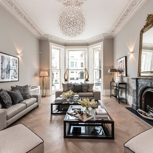 Inspiration for a traditional formal living room in London with beige walls, light hardwood flooring, a standard fireplace, a stone fireplace surround and no tv.