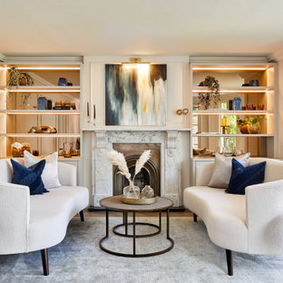 This is an example of a large contemporary formal enclosed living room in London with white walls, medium hardwood flooring, a standard fireplace, no tv, brown floors and panelled walls.