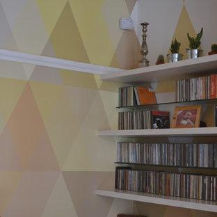 ロンドンの中サイズのミッドセンチュリースタイルのおしゃれな独立型リビング (ミュージックルーム、マルチカラーの壁、無垢フローリング、薪ストーブ、石材の暖炉まわり、据え置き型テレビ、茶色い床) の写真