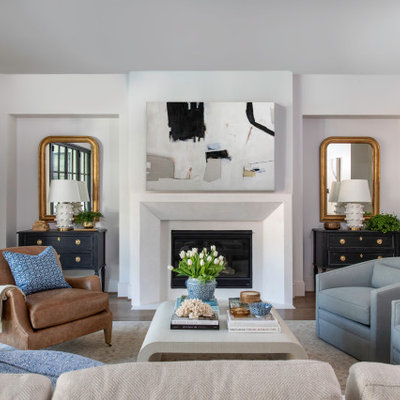 Large transitional formal medium tone wood floor living room photo in Houston with a plaster fireplace, white walls, a standard fireplace and no tv