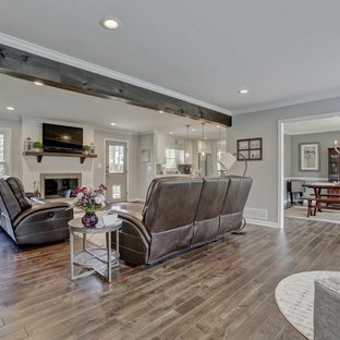 Large transitional open concept dark wood floor and brown floor living room photo in Atlanta with gray walls, a standard fireplace, a brick fireplace and a wall-mounted tv