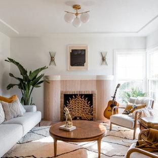 サクラメントのビーチスタイルのおしゃれなLDK (白い壁、淡色無垢フローリング、標準型暖炉、木材の暖炉まわり、ベージュの床) の写真