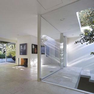 ロサンゼルスのコンテンポラリースタイルのおしゃれなリビングロフト (白い壁、トラバーチンの床、標準型暖炉、漆喰の暖炉まわり、白い床) の写真