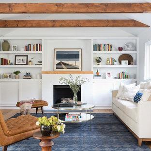 Cette image montre un salon traditionnel avec un mur blanc, un sol en bois brun, une cheminée standard, un manteau de cheminée en brique, un téléviseur fixé au mur et un sol marron.