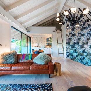 Diseño de salón tipo loft, bohemio, pequeño, con paredes multicolor, suelo de madera clara, chimenea de esquina, marco de chimenea de yeso, televisor colgado en la pared y suelo beige