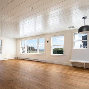Imagen de salón abierto y machihembrado, costero, pequeño, sin chimenea y televisor, con paredes blancas, suelo de madera en tonos medios y suelo marrón